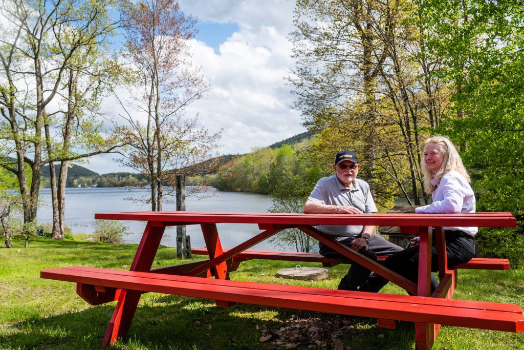 Couple sitting on red bench by lake